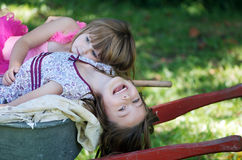 Two sisters on wheelbarrow Royalty Free Stock Photos