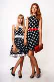 Two sisters on a white background. Two beautiful sisters in a black dress with white polka dots on a white background. Studio photo Royalty Free Stock Photo