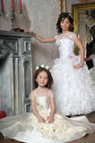 Two sisters in white evening dresses Stock Image