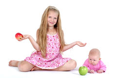Two sisters 8 year and 3 month ols with apple Royalty Free Stock Photos
