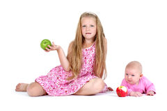 Two sisters 8 year and 3 month ols with apple Stock Images