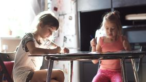 Two sisters 6 and 7 years drawing together sitting at the table. children draw with crayons in the sun. Children draw with pencils at home sitting at a table stock footage