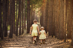 Two sisters in yellow dresses go through the forest holding hand Stock Image