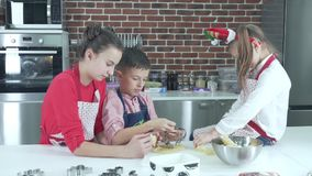 Two sisters and a younger brother preparing Christmas cookies. Children prepare cookies. Three children of different ages in the kitchen preparing Christmas stock video