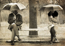 Two sitting at bench in rainy day. stock images