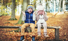 Two sitting children with their hands up Stock Images