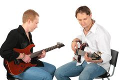 Two sitting men play on guitars Royalty Free Stock Image