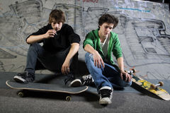 Two skateboarders sitting on ramp. In skatepark Royalty Free Stock Images