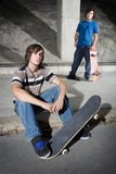 Two skateboarders in underground parking lot Royalty Free Stock Photos