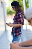 Two skaters using mobile phone in the street. Royalty Free Stock Image