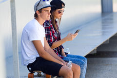 Two skaters using mobile phone in the street. Stock Photography