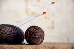 Two skeins of wool yarn and knitting needles. Two skeins of wool yarn in brown tones and knitting needles on an old wooden surface close-up, handmade, knitting royalty free stock photo