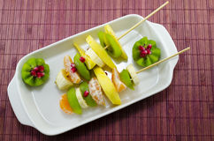 Two skewers full with colourful fruit. Two skewers full with colourful kiwis, bananas, oranges, pomegranade stock images
