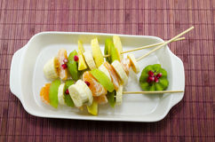 Two skewers full with colourful fruit. Two skewers full with colourful kiwis, bananas, oranges, pomegranade royalty free stock images