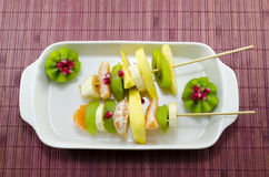 Two skewers full with colourful fruit on a table. Two skewers full with colourful kiwis, bananas, oranges, pomegranade stock photo