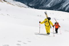 Two ski freerider climbs the slope into deep snow powder with the equipment on the back fixed on the backpack. The concept of winter extreme sports Royalty Free Stock Photography