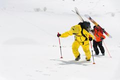 Two ski freerider climbs the slope into deep snow powder with the equipment on the back fixed on the backpack. The concept of winter extreme sports Stock Photo