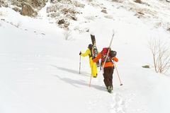 Two ski freerider climbs the slope into deep snow powder with the equipment on the back fixed on the backpack. The concept of winter extreme sports Stock Photography
