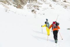 Two ski freerider climbs the slope into deep snow powder with the equipment on the back fixed on the backpack. The concept of winter extreme sports Royalty Free Stock Photos