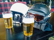 Two ski helmets enjoying two beers royalty free stock photography
