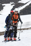 Two ski mountaineers climb on mountain on skis strapped to climbing skins Stock Photography