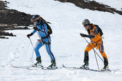 Two ski mountaineers climb on mountain on skis strapped to climbing skins Royalty Free Stock Photos
