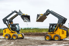 Two skid steers with raiced bucket outdoors Stock Photos