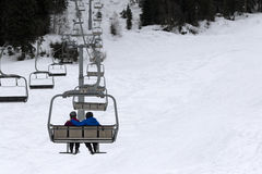 Two skiers on chair-lift in gray day Stock Images