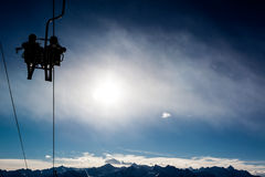 Two skiers in a chairlift backlit by the sun. Royalty Free Stock Photos