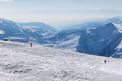Two skiers downhill on snow off-piste slope and mountains in haz Stock Images