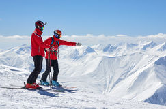 Two skiers are on edge of a cliff in mountains Stock Photography