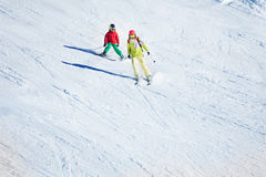 Two skiers hitting the slopes at snowy mountains stock image