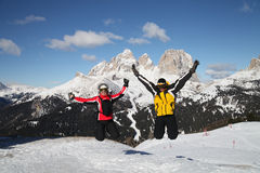 Two skiers jump on top of mountain. In Dolomites Alps stock photo