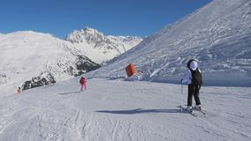Two Skier Woman Skiing Carving Style On The Mountain Slope In Winter. Two skiers ladies skiing carving style down the ski slope slowly and gracefully at a ski stock video