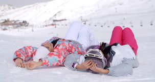 Two skiers laying on the ground. Two women in skiing snowsuits laying on their backs on snow at bottom of ski slope as if to sunbathe with mountain behind them stock footage