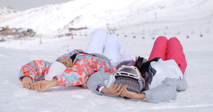 Two skiers laying on the ground Stock Photo