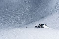 Snow covered alpine mountain hut with two skiers in winter Royalty Free Stock Image