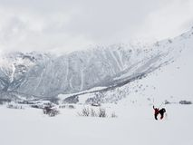 Two skiers in a mountain landscape in bad weather in winter royalty free stock images