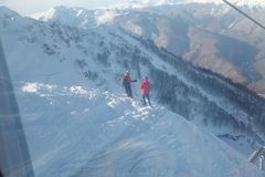 Two skiers are on the precipice of the snow mountain stock photography