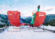 Two skiers relax in chiars on the mountain top Royalty Free Stock Image