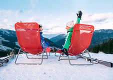 Two skiers relax in chiars on the mountain top Stock Photos