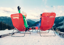 Two skiers relax in chiars on the mountain top Stock Image