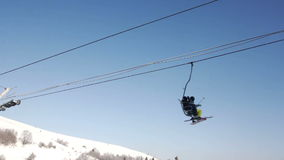 Two skiers riding up ski lift stock footage