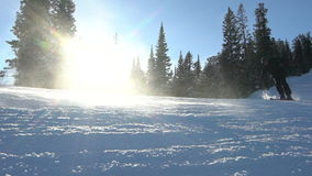 Two skiers skiing slope on sunny winter day stock video footage