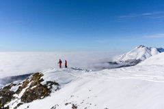 Two skiers on top of mountain above the clouds Stock Photos