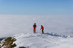 Two skiers on top of mountain above the clouds Stock Photo