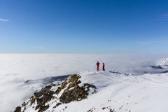 Two skiers on top of mountain above the clouds Royalty Free Stock Photo