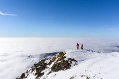 Two skiers on top of mountain above the clouds Royalty Free Stock Photos