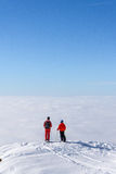 Two skiers on top of mountain above the clouds Stock Image