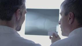 Two skill doctors checking x-ray, discussing. The man in white robe talking about human bones in laboratory. Concept of